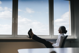 Businesswoman in office sitting at the window looking outの写真素材 [FYI04347258]