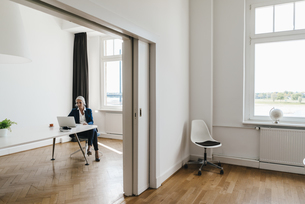 Businesswoman working on laptop in officeの写真素材 [FYI04347261]