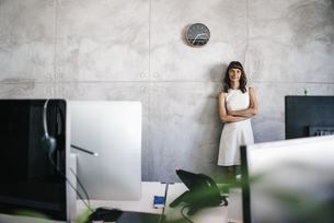 Businesswoman standing under wall clock with arms crossedの写真素材 [FYI04347399]