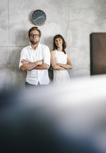 Business partners standing in office under wall clockの写真素材 [FYI04347403]