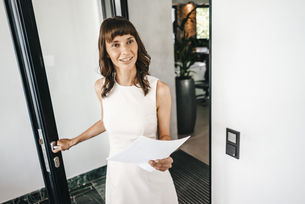 Businesswoman entering office, holding documentsの写真素材 [FYI04347407]