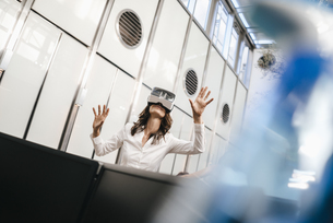 Businesswoman using VR goggles in officeの写真素材 [FYI04347445]