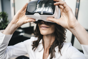 Businesswoman using VR goggles in officeの写真素材 [FYI04347446]