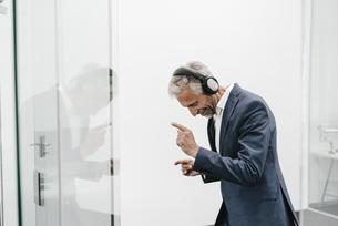 Happy mature businessman in office wearing headphonesの写真素材 [FYI04347520]