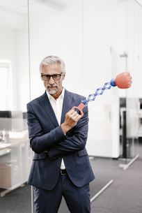 Mature businessman in office holding boxing toyの写真素材 [FYI04347579]