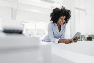 Smiling young woman using tablet in officeの写真素材 [FYI04347658]