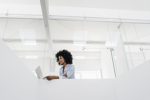 Young woman using laptop in officeの写真素材 [FYI04347659]