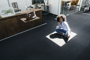 Young woman sitting on floor in officeの写真素材 [FYI04347660]