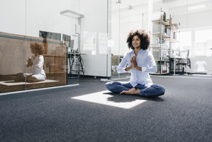 Young woman doing yoga in officeの写真素材 [FYI04347661]