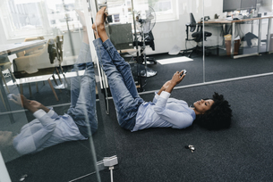 Young woman lying on the floor in office checking cell phoneの写真素材 [FYI04347663]