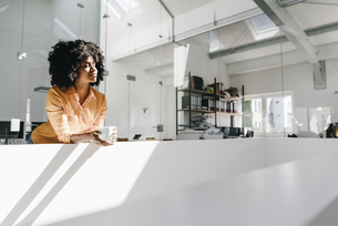 Young woman having a coffee break in officeの写真素材 [FYI04347675]