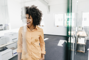 Excited young woman screaming in officeの写真素材 [FYI04347676]