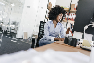 Laughing young woman working at desk in officeの写真素材 [FYI04347679]