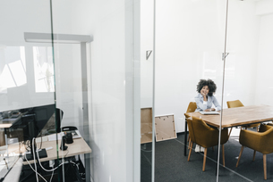 Portrait of young woman sitting at table in officeの写真素材 [FYI04347680]