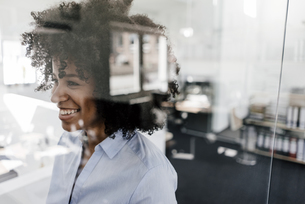 Smiling young woman behind glass wall in officeの写真素材 [FYI04347682]