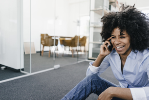 Laughing young woman on cell phone in officeの写真素材 [FYI04347683]