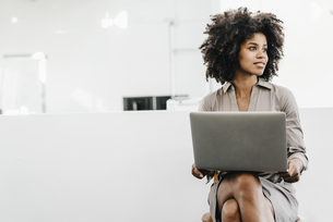 Young woman using laptop in officeの写真素材 [FYI04347691]