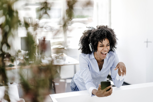 Happy young woman listening to music in officeの写真素材 [FYI04347707]