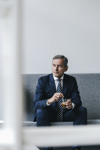 Mature businessman with glass of coffee sitting on couch inの写真素材 [FYI04347751]
