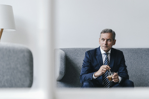 Mature businessman with glass of coffee sitting on couch inの写真素材 [FYI04347752]