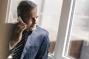 Smiling mature businessman on cell phone looking out of windの写真素材 [FYI04347754]