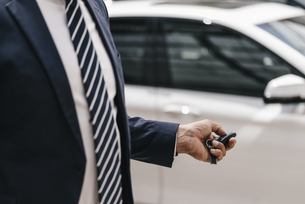 Businessman using remote control key of car, partial viewの写真素材 [FYI04347758]