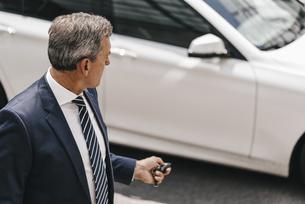 Businessman using remote control key of carの写真素材 [FYI04347759]