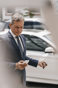 Businessman checking message while using remote control keyの写真素材 [FYI04347760]