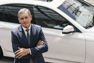 Portrait of mature businessman standing in front of carの写真素材 [FYI04347761]