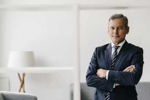Portrait of mature businessman with arms crossed in his offiの写真素材 [FYI04347762]