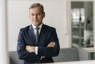 Portrait of mature businessman with arms crossed in his offiの写真素材 [FYI04347763]