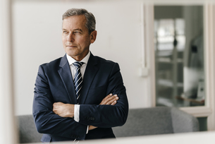 Portrait of mature businessman with arms crossed in his offiの写真素材 [FYI04347765]