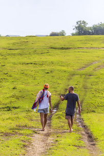 Back view of couple walking barefoot on a meadowの写真素材 [FYI04347767]