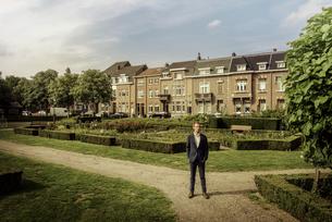 Netherlands, Venlo, businessman standing in city parkの写真素材 [FYI04347775]