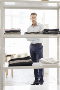 Portrait of confident businessman standing at shelf with cloの写真素材 [FYI04347792]