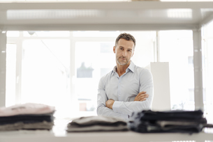 Portrait of confident businessman standing at shelf with cloの写真素材 [FYI04347793]
