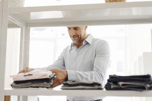Businessman sorting clothes on shelfの写真素材 [FYI04347794]