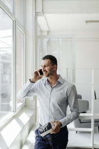 Businessman on cell phone at the window holding VR glassesの写真素材 [FYI04347825]