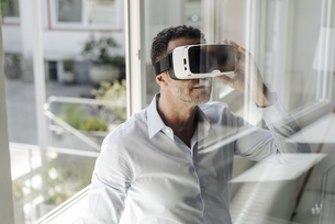 Businessman at the window wearing VR glassesの写真素材 [FYI04347831]