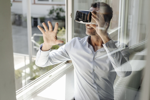 Businessman at the window wearing VR glassesの写真素材 [FYI04347834]