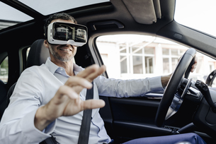 Businessman wearing VR glasses driving a carの写真素材 [FYI04347840]