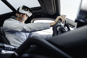Businessman wearing VR glasses driving a carの写真素材 [FYI04347842]