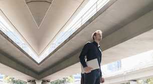 Businessman standing at underpass holding laptop, compositeの写真素材 [FYI04347843]