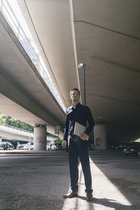 Businessman standing at underpass holding laptopの写真素材 [FYI04347844]