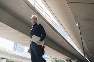 Businessman standing at underpass holding laptopの写真素材 [FYI04347846]