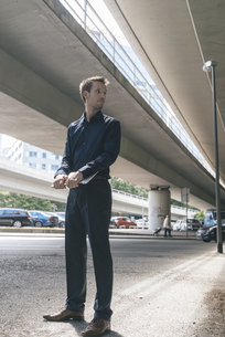 Businessman standing at underpass holding laptopの写真素材 [FYI04347847]