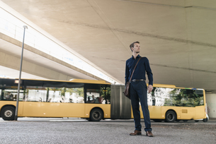Businessman standing at underpass with bus in backgroundの写真素材 [FYI04347849]