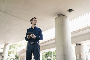Businessman standing at underpass holding tabletの写真素材 [FYI04347850]