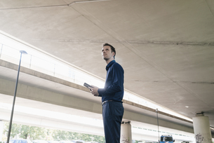 Businessman standing at underpass holding tabletの写真素材 [FYI04347853]