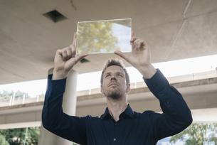 Businessman holding up portable glass deviceの写真素材 [FYI04347859]